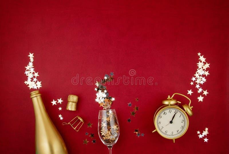 Gouden fles van champagne, glas, wekker en confettie over de rode achtergrond Partij, nieuw jaar, Kerstmisviering stock foto