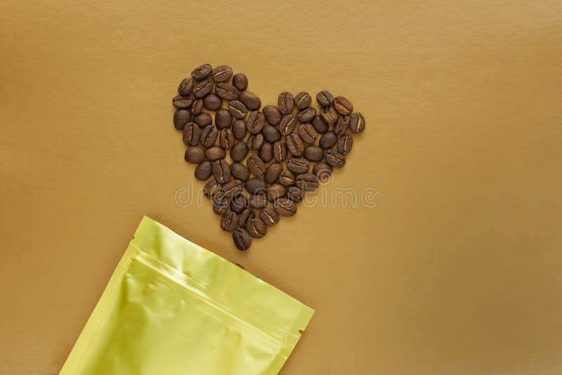 Gouden foliezak met koffiebonen op gouden achtergrond verpakkend malplaatjemodel Aluminiumpakket voor flatlay thee, stock foto's