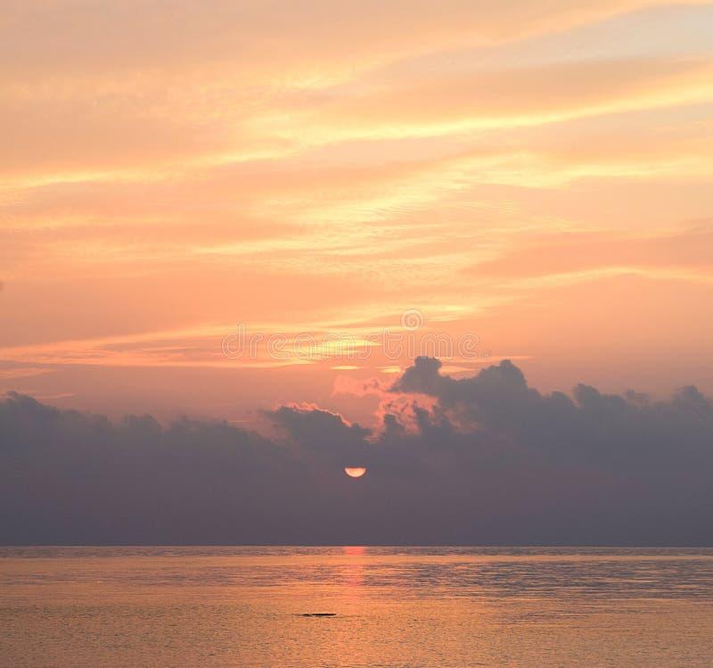 Gouden Gele Lijnen in Wolken in Ochtendhemel met het Toenemen Zon bij Horizon over Oceaan - Warme Skyscape royalty-vrije stock foto's