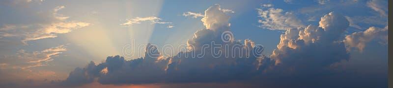 Gouden Gele Schemerige Zonstralen van Donkere Wolken in Blauwe Hemel - Natuurlijke Achtergrond Skyscape stock afbeeldingen