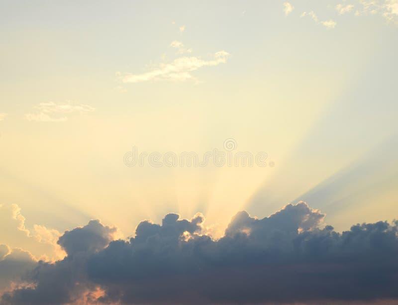 Gouden Gele Schemerige Zonstralen van Donkere Wolken in Heldere Hemel - Natuurlijke Achtergrond Skyscape stock fotografie