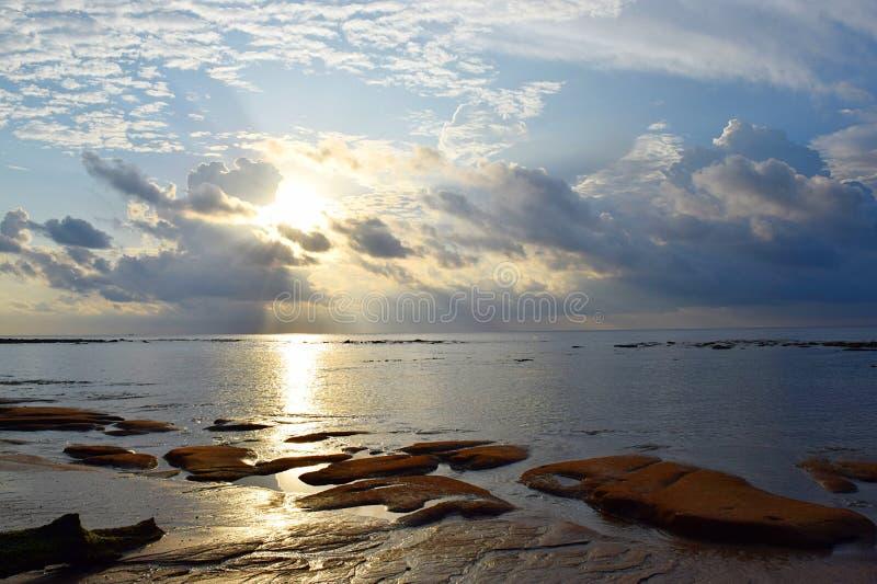 Gouden Gele Zon met Helder Zonlicht die van achter Wolken met Bezinning in Zeewater - Ochtendhemel bij Strand toenemen royalty-vrije stock foto's