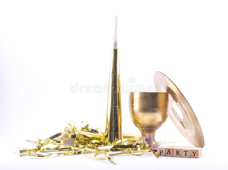 Gouden geschilderd partijfluitje, glas, schijf met het teken - partij op een witte achtergrond - stilleven stock foto's