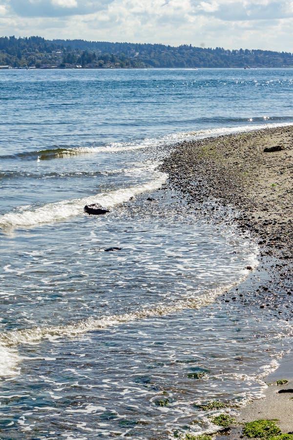 gouden golven gelaagd over een grintkust stock afbeeldingen