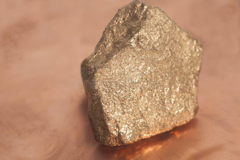 Gouden goudklompje op koperachtergrond stock fotografie