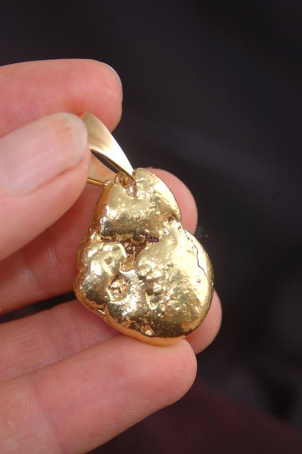 Gouden goudklompjetegenhanger stock foto