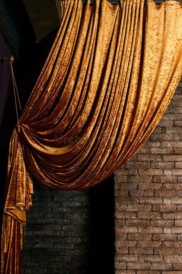 Gouden groot gordijn op bakstenen muur stock afbeeldingen
