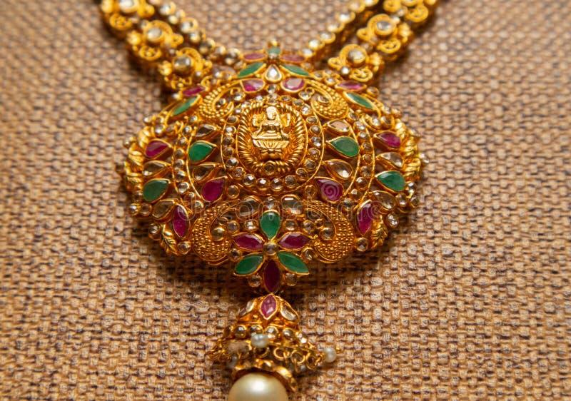 Gouden Guttapusalu-Halsband met halfedelstenen traditionele Indische huwelijksjuwelen op houten geweven achtergrond royalty-vrije stock afbeelding