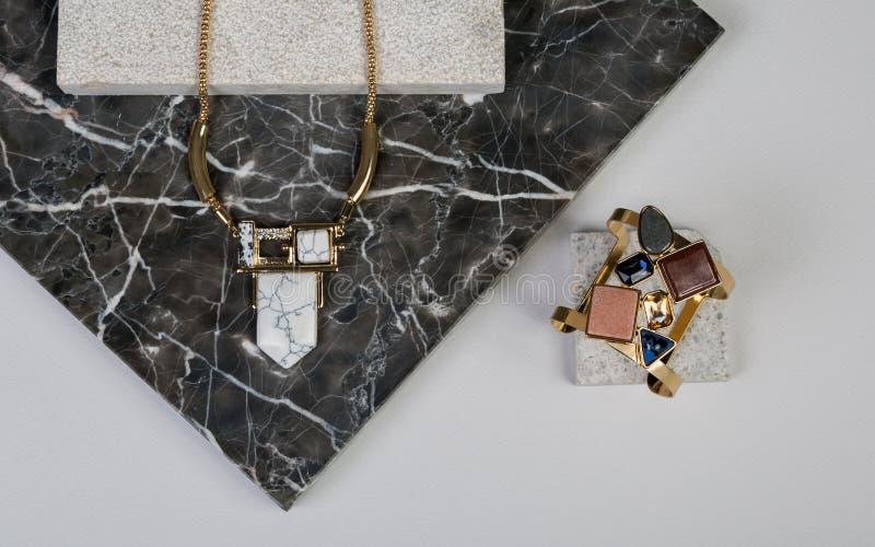 Gouden halsband en armband op donkere granit natuurlijke rots stock fotografie