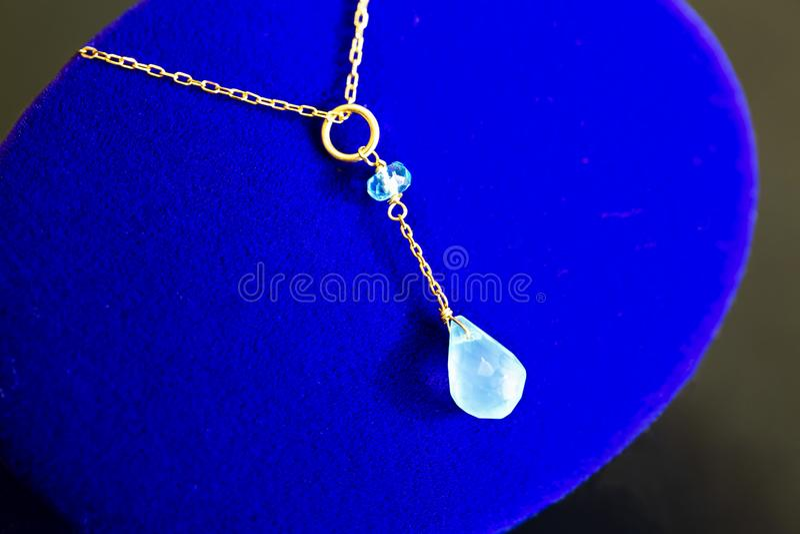 Gouden halsband met apatite met groene chalcedony met blauwe topaas op blauw juwelengeval royalty-vrije stock afbeeldingen