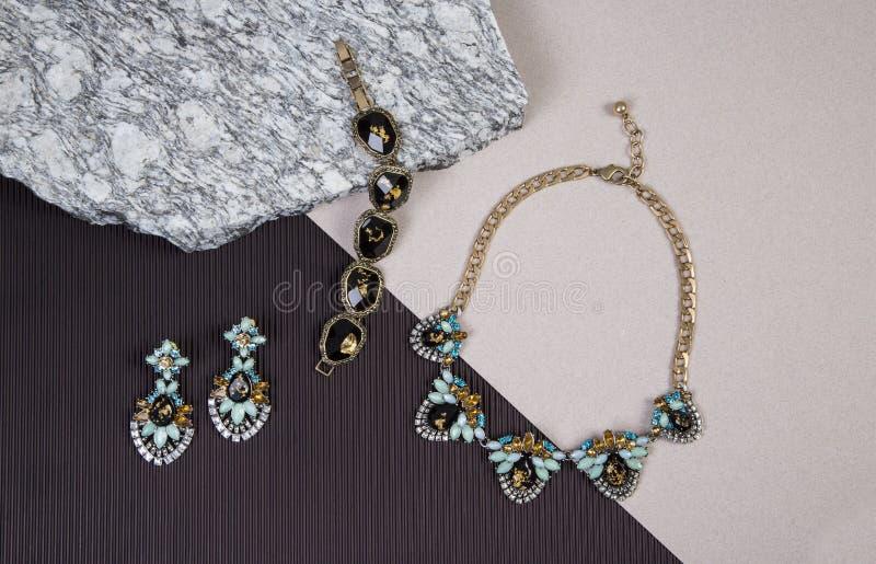 Gouden Halsbandketting en armband op graniet stock foto