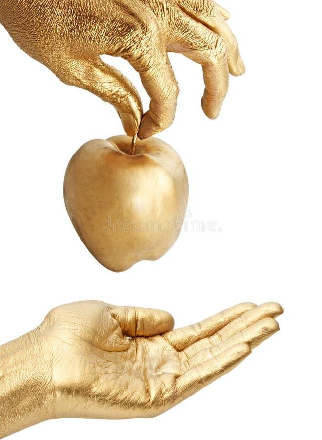 Gouden hand die appel geeft stock afbeeldingen