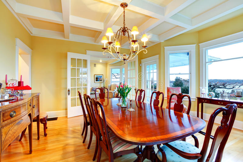 Gouden heldere gele luxeeetkamer met elegant klassiek meubilair. stock foto