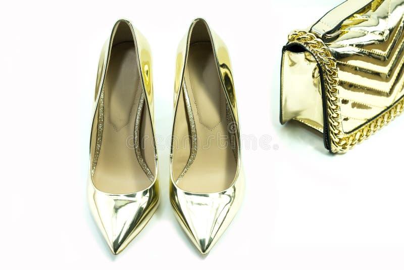 Gouden hoge hielschoenen en zak voor dame stock afbeeldingen