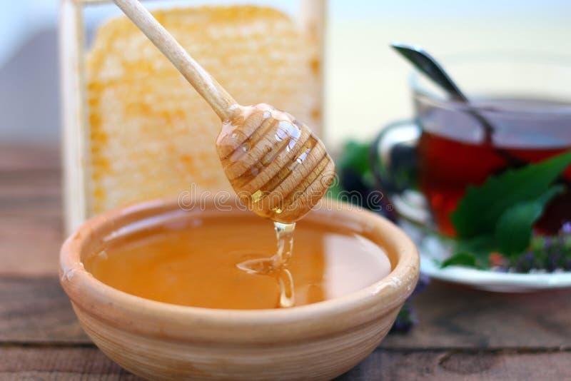 Gouden honing in een kleikom met geurige thee en honingraten royalty-vrije stock fotografie
