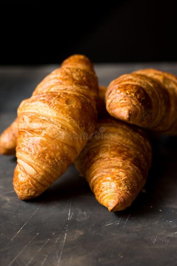 Gouden hoop van vers gebakken croissants op zwarte achtergrond, - de heerlijke korst, sluit omhoog stock afbeeldingen