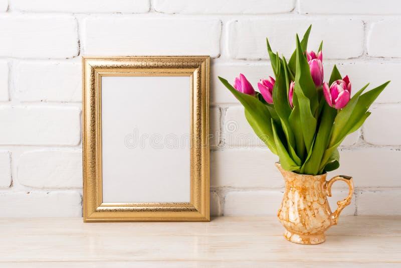 Gouden kadermodel met magenta roze tulpen in gouden vaas stock foto