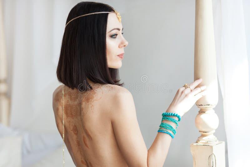 Gouden ketting in de handen van een jonge aantrekkelijke oosterse vrouw Vertroebelende achtergrond royalty-vrije stock foto