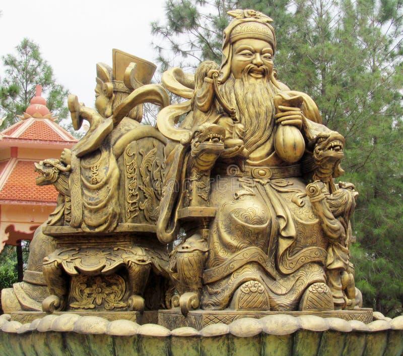 Gouden-kleurenstandbeeld van de Aziatische mens stock fotografie