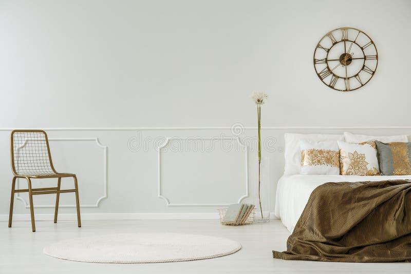 Gouden klok boven bed met deken in wit slaapkamerbinnenland met stoel en paardebloem Echte foto stock fotografie