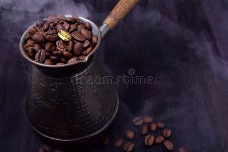 Gouden koffieboon op vers geroosterde degenen in een Turkse koffiepot stock afbeeldingen