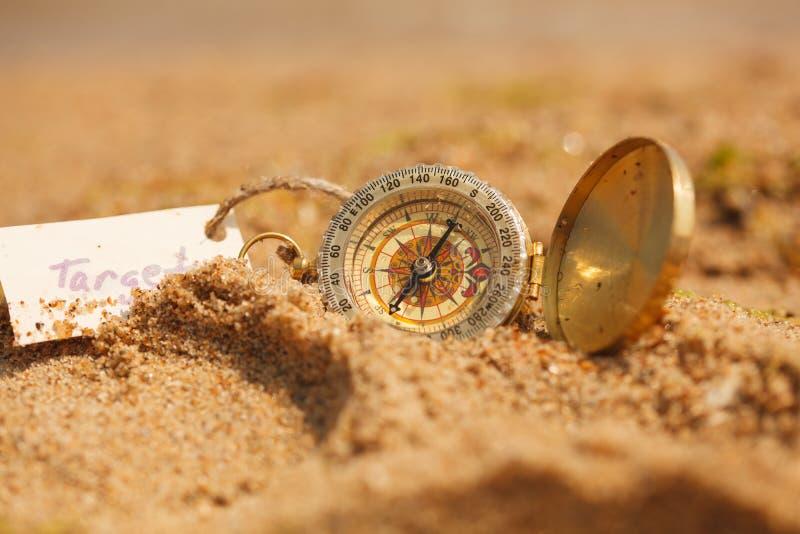 Gouden kompas met strandzand in close-up stock fotografie