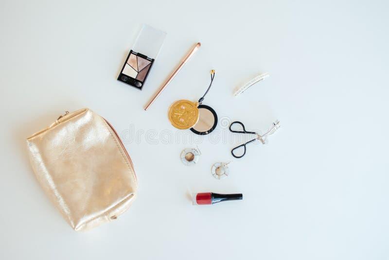 Gouden kosmetische zak met kosmetische schoonheidsproducten royalty-vrije stock foto