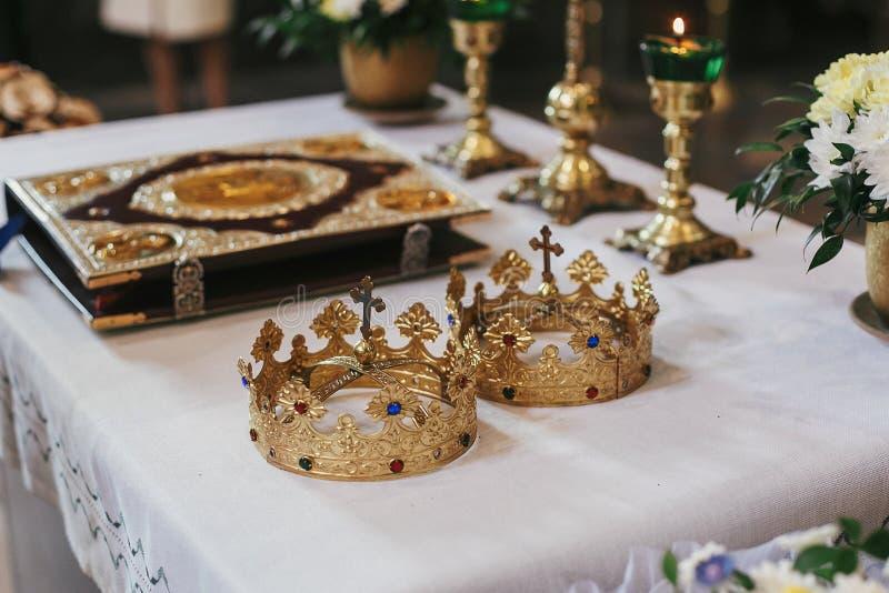 Gouden kronen en bijbel op heilig altaar tijdens huwelijksceremonie binnen stock fotografie
