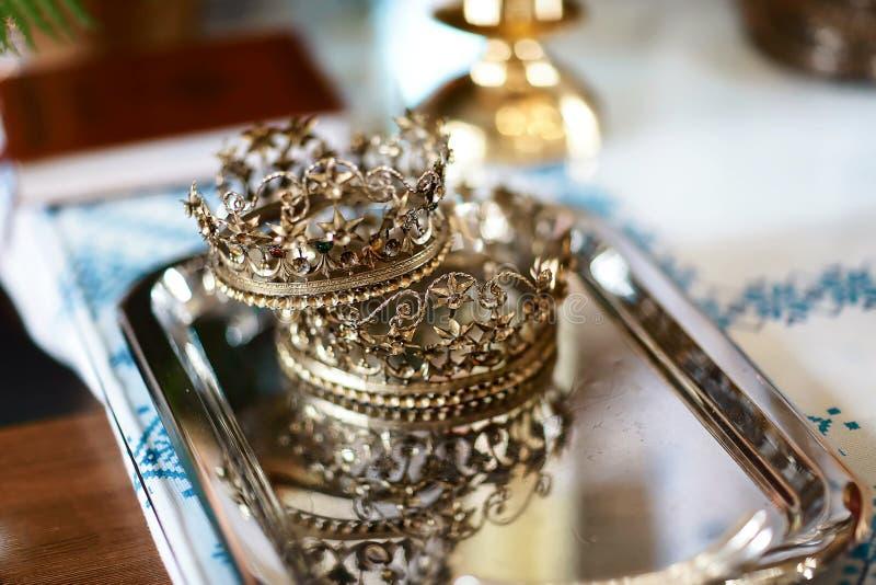 Gouden kroon bij het altaar in de kerk voor de traditionele godsdienstige het huwelijksceremonie van het huwelijkspaar stock foto