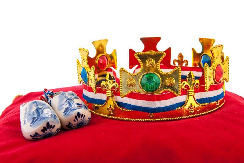 Gouden kroon op fluweelhoofdkussen met Nederlandse houten schoenen royalty-vrije stock fotografie