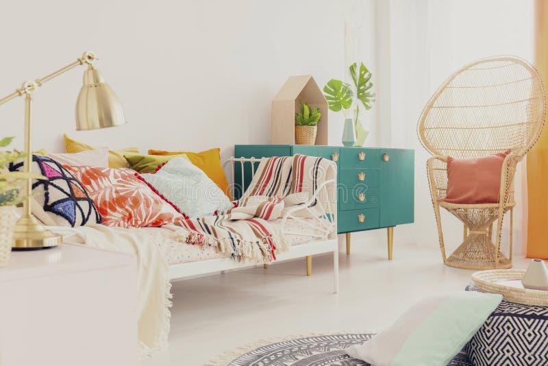 Gouden lamp op nightstand in de slaapkamer van het bohomeisje met kleurrijk beddegoed op bed, groene houten kabinet en pauwstoel  royalty-vrije stock afbeelding