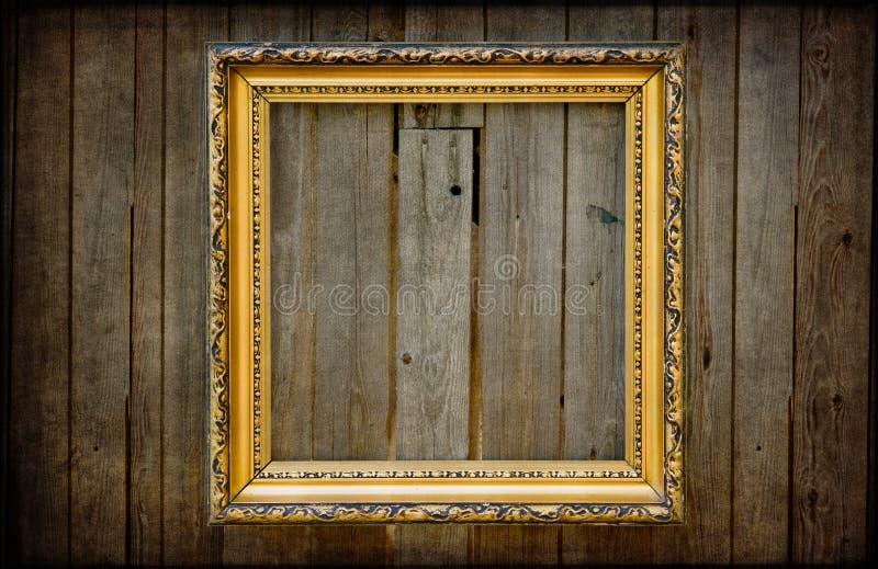 Gouden leeg frame op een houten rustieke muur stock afbeeldingen