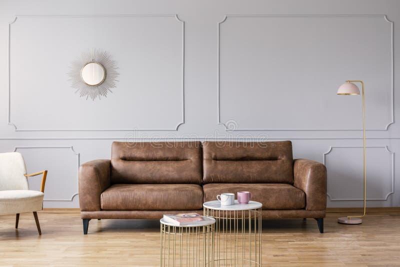 Gouden lijsten voor leerbank in grijs elegant woonkamerbinnenland met spiegel en lamp stock afbeeldingen
