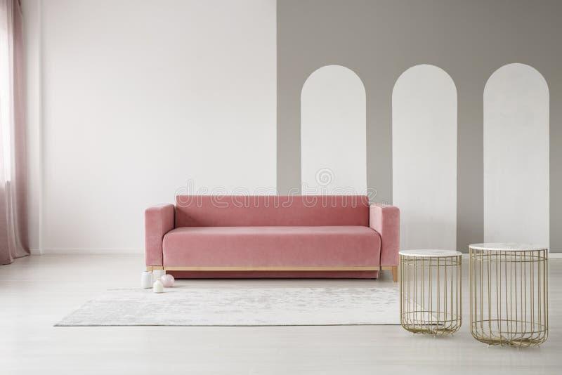 Gouden mandlijsten en een roze bank in een elegant woonkamerbinnenland met grijze bogen op een witte muur stock afbeeldingen