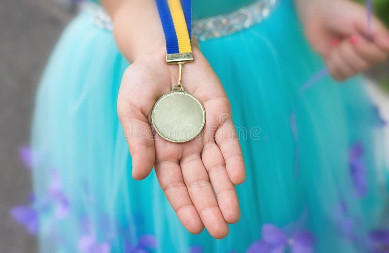 Gouden medaille bij meisjeshand Een diploma behaald van kleuterschool royalty-vrije stock afbeeldingen