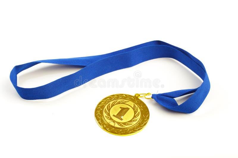 Gouden medaille in de voorgrond op blauw lint stock afbeeldingen