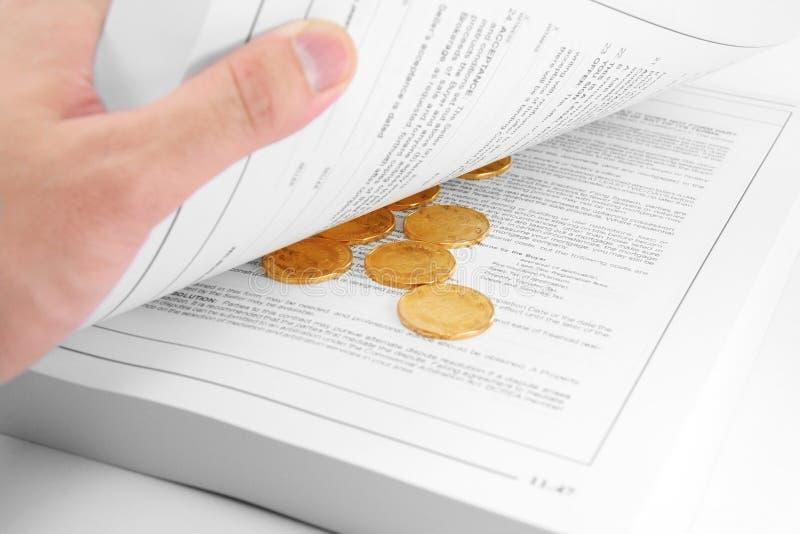 Gouden muntstuk en boek stock afbeeldingen