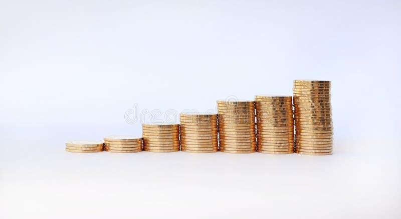 Gouden muntstukken en zwarte pijlgrafiek omhoog op witte achtergrond stock foto