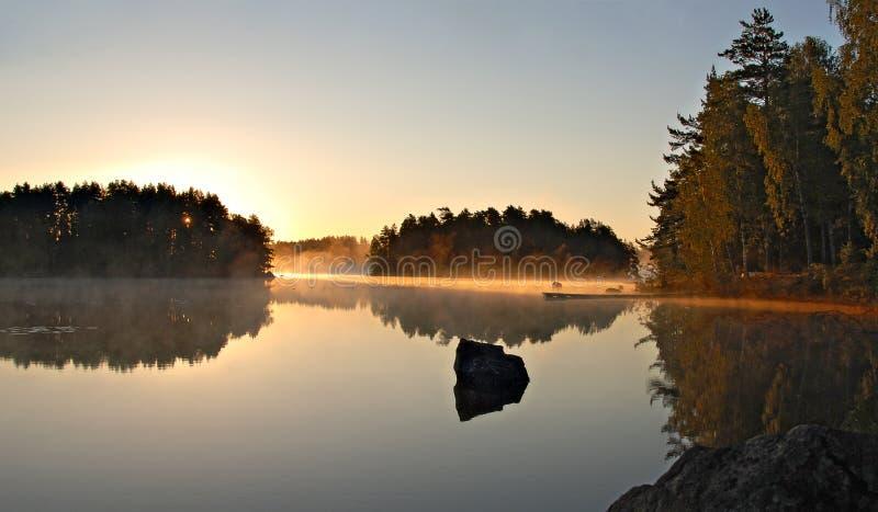 Gouden ochtendzon op een Zweeds meer stock foto's