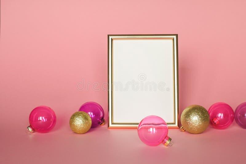 Gouden omlijsting met Kerstmisornamenten Model op roze achtergrondmanierdecoratie royalty-vrije stock fotografie