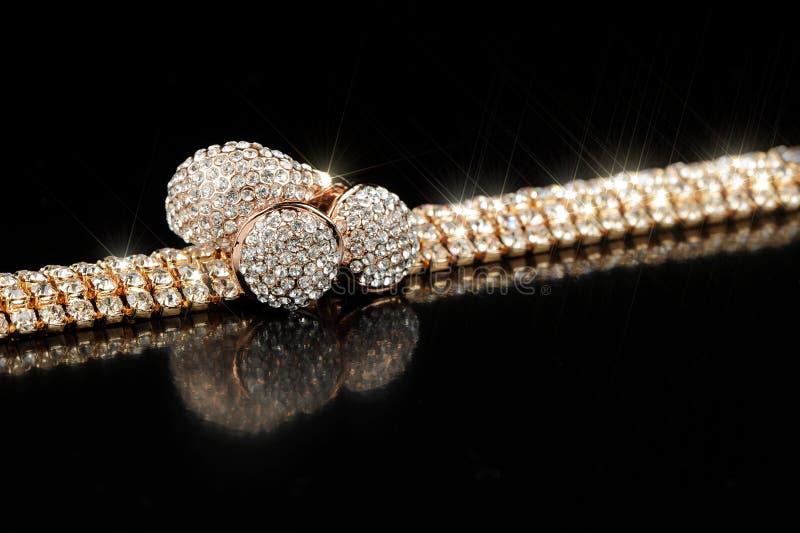 Gouden Oorringen, Armband en Ring met Glanzende Stenen op Zwarte Achtergrond stock afbeeldingen