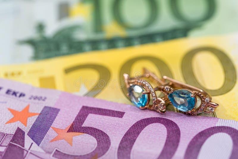 gouden oorringen die op euro liggen stock afbeeldingen