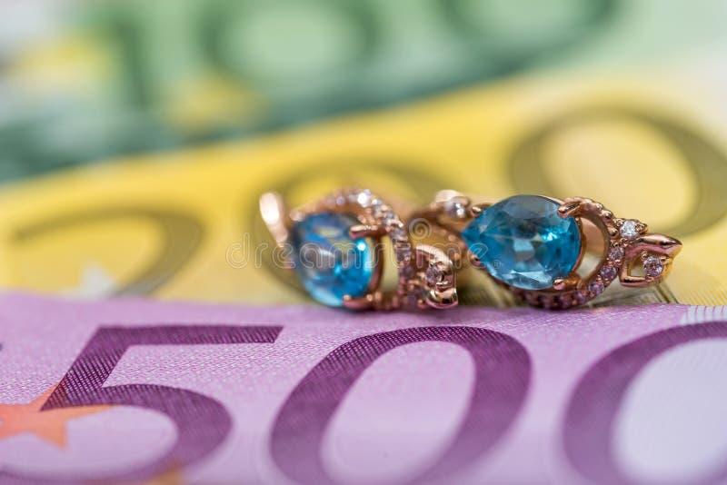 gouden oorringen die op euro liggen royalty-vrije stock foto's