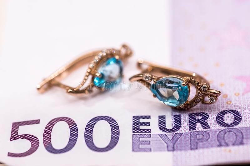 gouden oorringen die op euro liggen royalty-vrije stock afbeelding