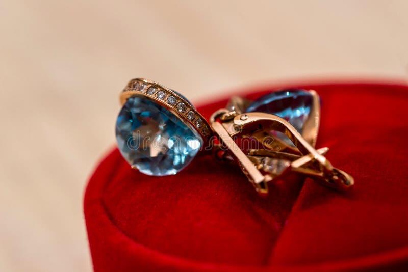 Gouden oorringen met kristal stock afbeeldingen