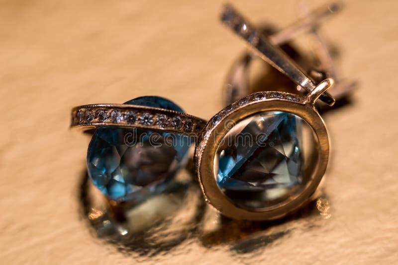 Gouden oorringen met kristallen op achtergrond stock foto