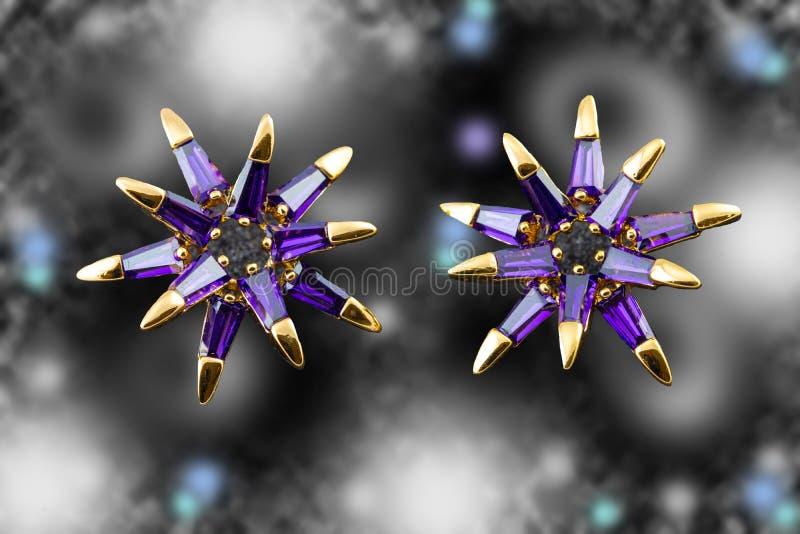 Gouden oorringen met purpere kristallen De juwelen van de luxemanier Bokeh backround royalty-vrije stock afbeeldingen