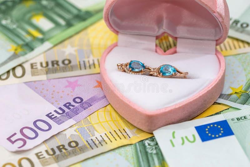 gouden oorringen op euro rekeningen stock fotografie