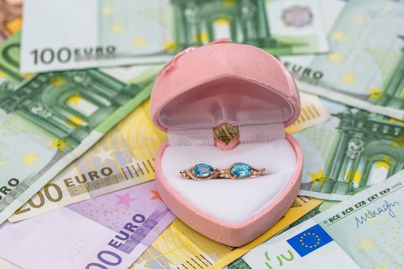 gouden oorringen op euro rekeningen stock afbeelding