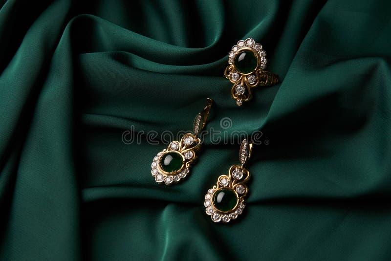 Gouden ring en paar oorringen met groene Smaragd en Diamanten stock afbeeldingen
